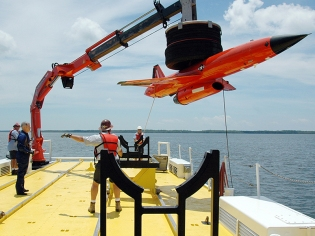 The crew from Florida Offshore steadies and lowers the BQM-167 sub-scale drone to the cradle after a recovery demonstration July 22 in the waters off Tyndall Air Force Base, Fla. The ship used for recovery is one of only three 120-foot boats owned by the Air Force. The Florida Offshore crew is contracted through the 82nd Aerial Targets Squadron to help recover sub-scale drones after they are shot down during live-fire exercises. (U.S. Air Force photo/Samuel King Jr.)